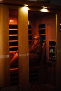 Sauna Benefits by popular Colorado massage blog, Camino Massage: image of a woman standing in a sauna.
