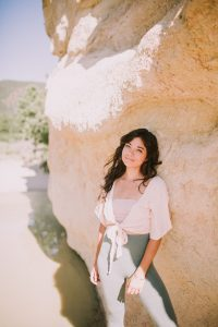 Massage Therapist by popular Colorado Springs Massage Therapist, Camino Massage: image of a woman leaning against a rock formation and wearing a cream wrap top and olive leggings.